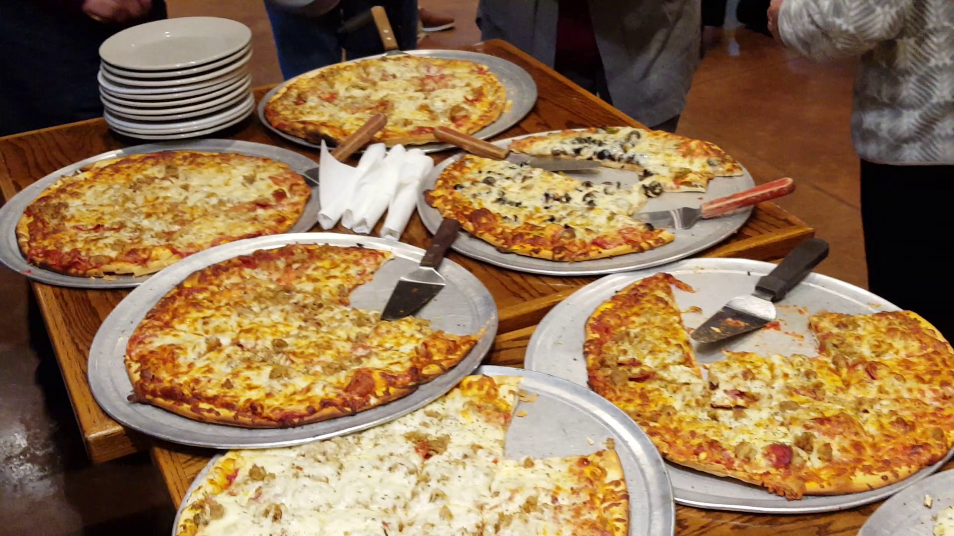 2 tables with 6 different pizzas, serving utensils, plates, and silverware.